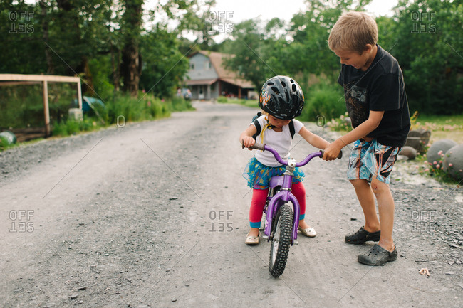 Boy teaching his sister to ride a bicycle