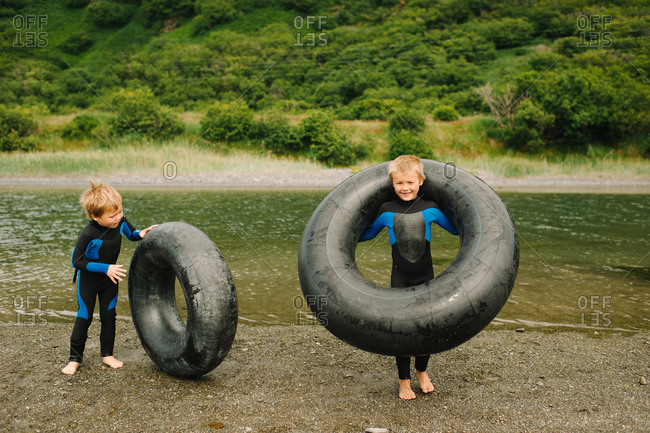 Children playing with inner tubes on the riverbank