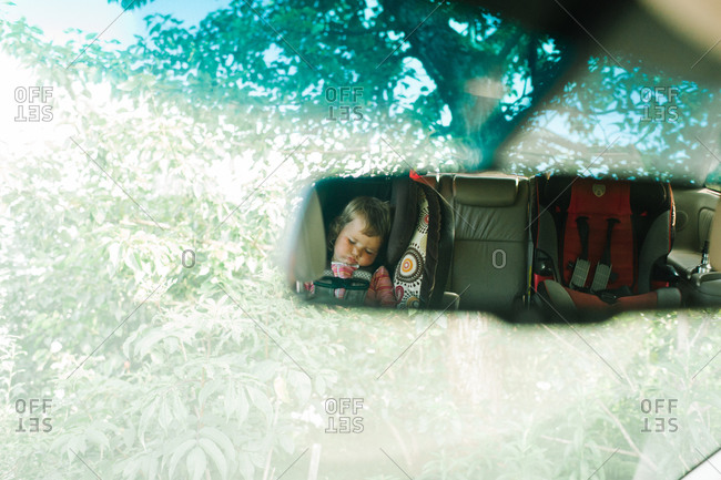 Reflection of a sleeping girl in a car