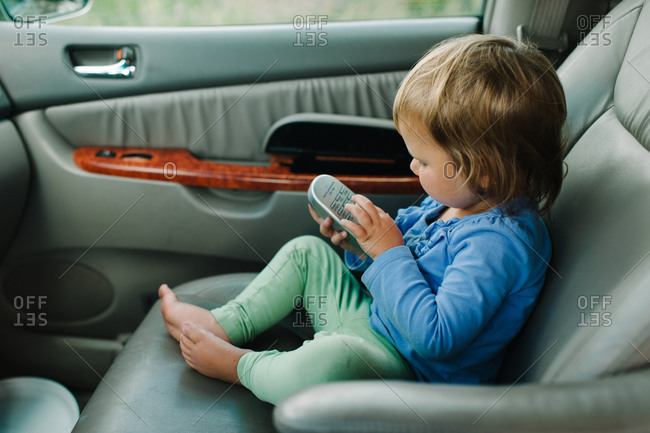 Little girl examining a remote control in a car