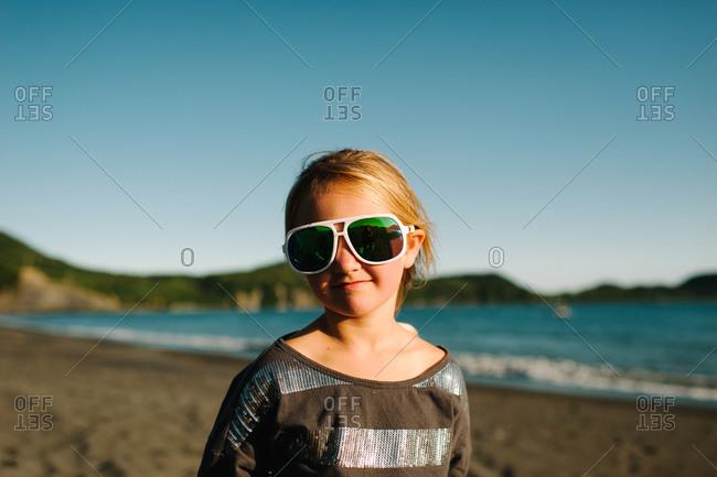 Girl wearing oversized sunglasses on the beach