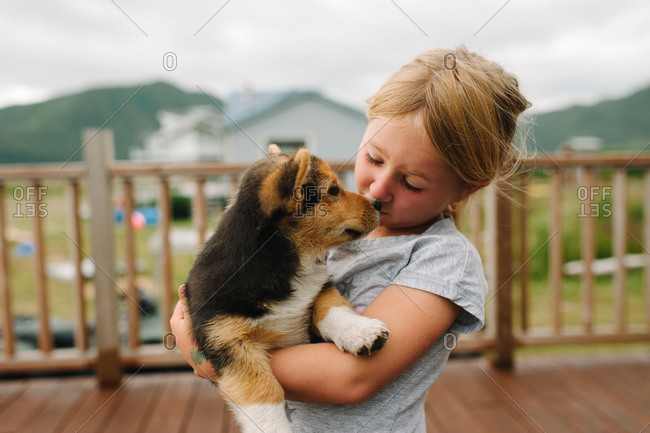 Girl holding a puppy in her arms