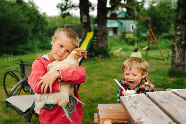 Boy hugging a chicken in a garden