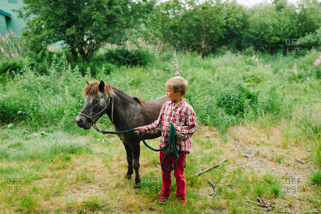Boy leading a pony on a leash
