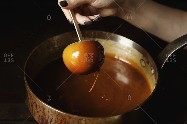 Close up of woman dipping an apple into caramel sauce