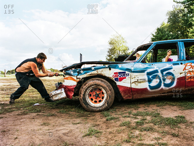 White lake, New York, USA - March 6, 2006: Man rips off a part of the car hoof at Demolition derby