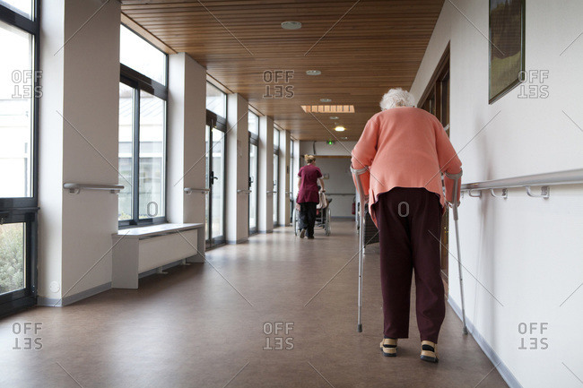 Rear view of an elderly lady using a stroller in a retirement home.