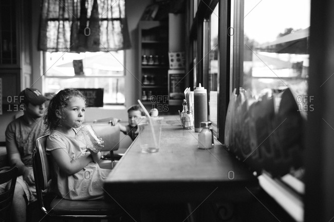 Young girl slurping in a restaurant