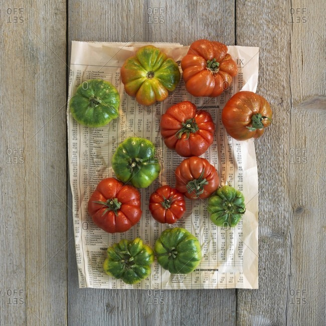 Red and green beefsteak tomatoes on a piece of newspaper
