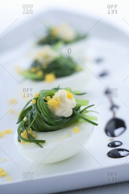 Eggs filled with buck's horn plantain and sprinkled with egg yolk with balsamic vinegar