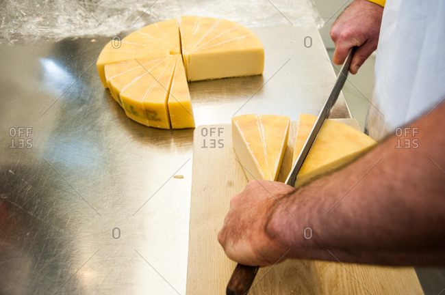 High angle view of man cutting cheese