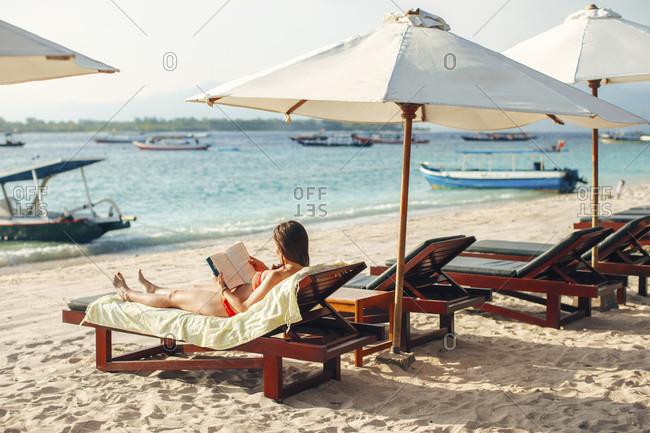 Woman lying on a beach chair reading a book