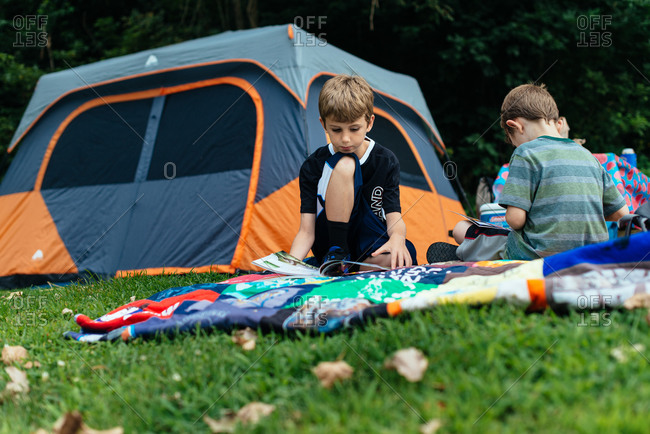 Boys reading magazines at a camping tent