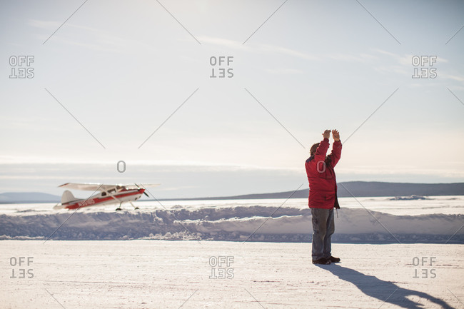 Man signaling for an airplane in a snowy field