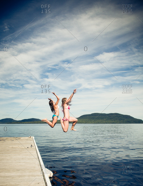 Young women jumping into Moosehead Lake, Maine
