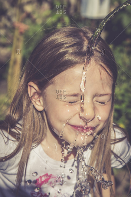 Little girl refreshing her face with a jet of water