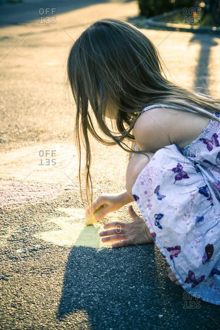 Little girl painting with crayons on tarmac