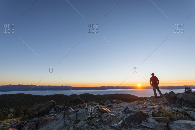 Wide angle view of a man watching the sunset over Lake Tahoe from the top of Genoa Peak, Nevada