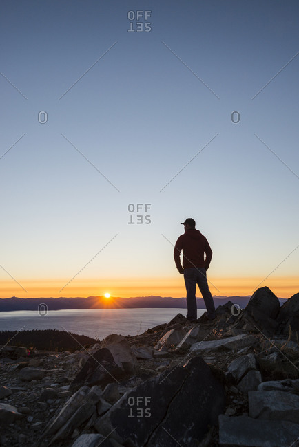 Man with arms akimbo watching the sunset over Lake Tahoe from the top of Genoa Peak, Nevada.