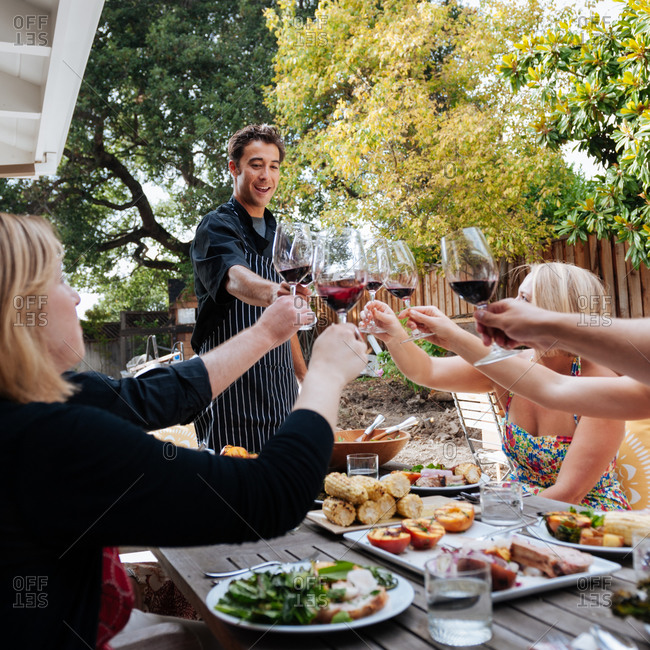 Friends toasting with personal chef on the patio
