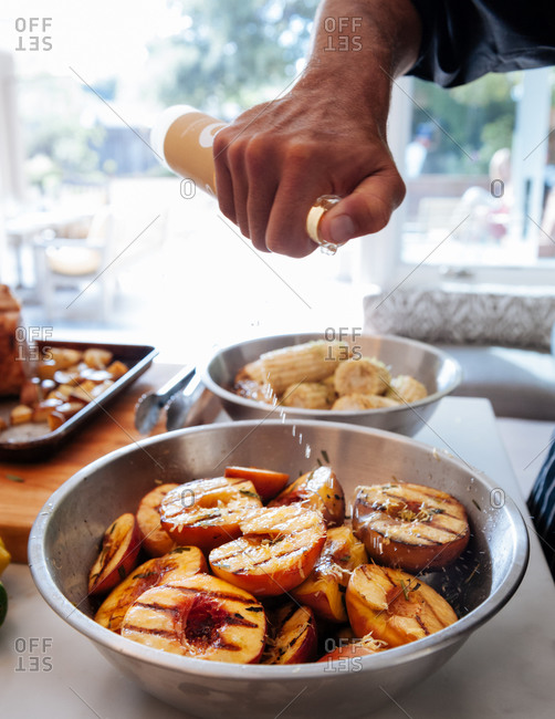 Grilled peaches being seasoned with champagne vinegar in the kitchen