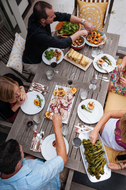 Friends enjoying a meal at a summer table on their patio prepared by a personal chef