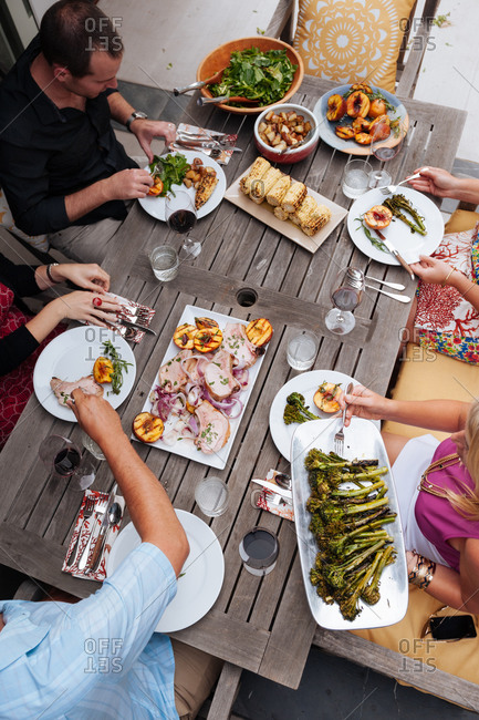 Overhead view of friends enjoying a meal at a summer table on their patio prepared by a personal chef