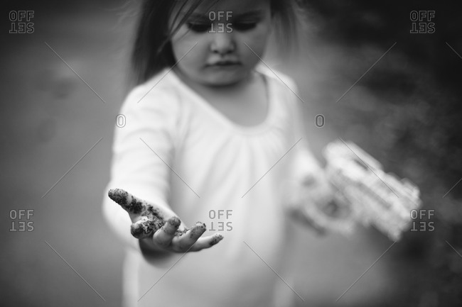 Little girl showing dirt on his hand