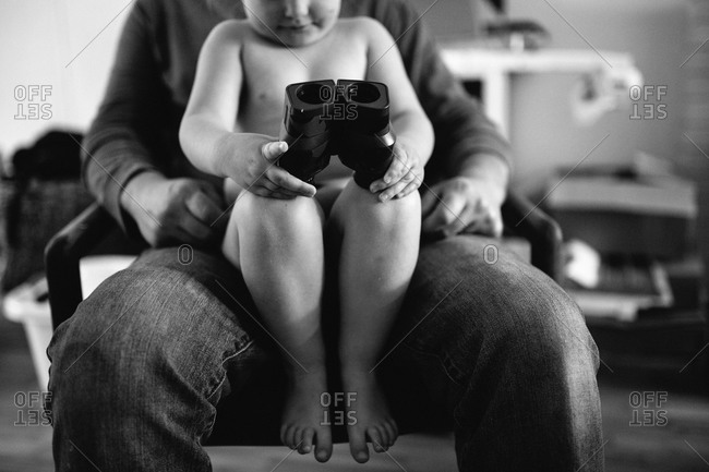 Girl holding binoculars in her father's lap