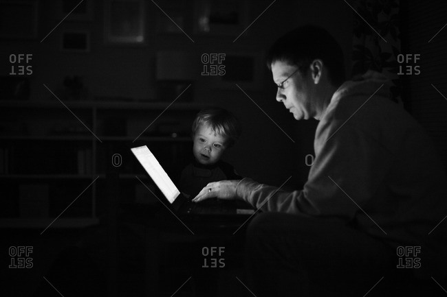 Curious little boy watching his father while working on computer
