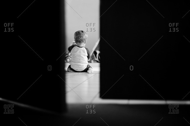 Rear view of little boy playing on the floor