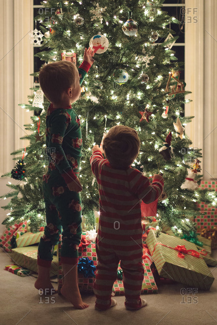 Brothers in pajama staring a decorated Christmas tree