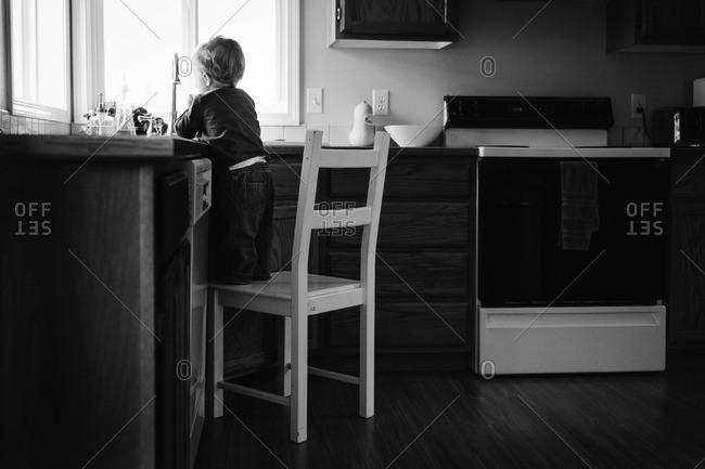 Boy standing on chair and washing his hands in the kitchen