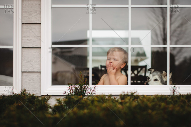 View of boy blowing kiss through window