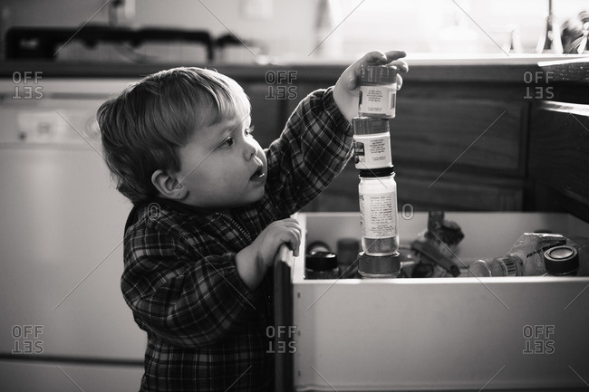 Boy stacking bottle of spices in the kitchen