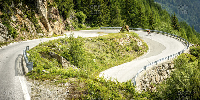 Cyclist taking a hairpin turn in the Alps, Switzerland
