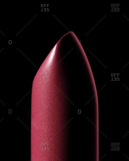Pink metallic lipstick on black background