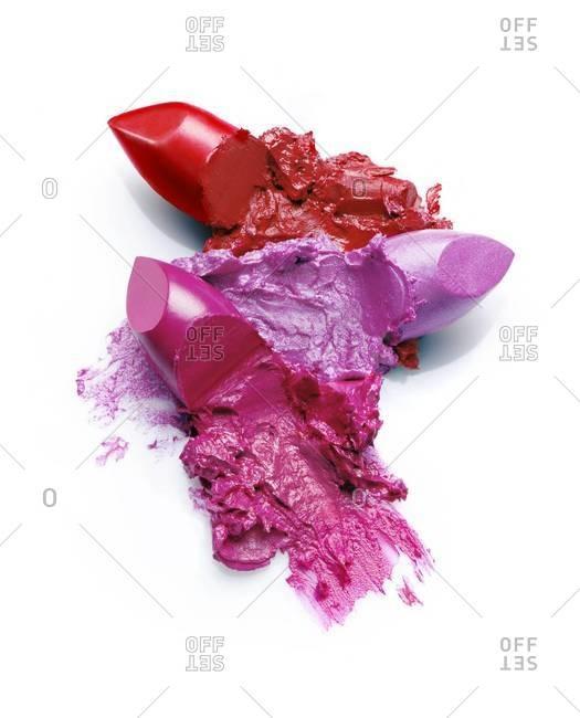 Mashed lipstick tips on white background