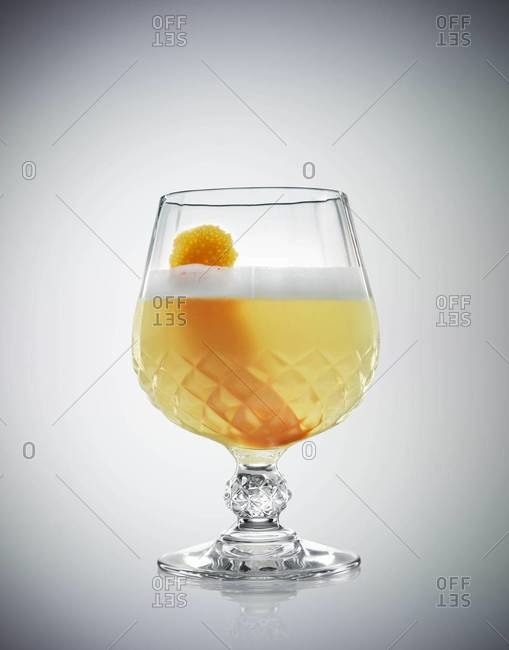 Studio shot of a whiskey sour with orange twist