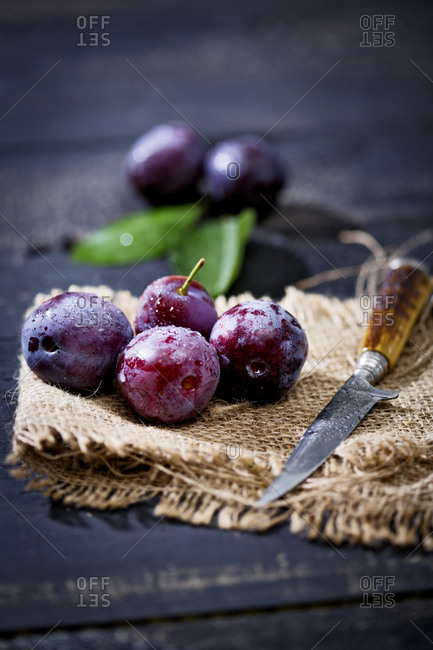 Plums, Prunus domestica, and knife on jute and dark wood