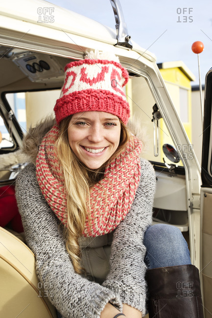 Smiling girl sitting on the front passenger seat of a camper