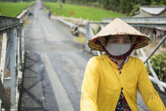 Sa Dec, Vietnam - June 27, 2013: Asian woman riding a bike in Sa Dec, Vietnam