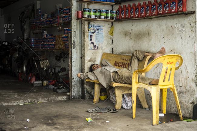 Soc Trang, Vietnam - June 26, 2013: Man resting on a bench in a garage