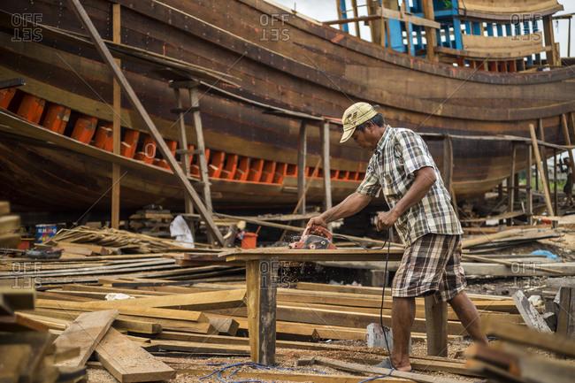 Soc Trang, Vietnam - June 24, 2013: Shipwright sanding a board in a shipyard, Vietnam