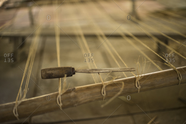 Close up of a chisel on stretched out strings