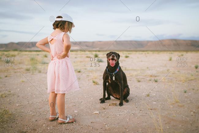 Young girl looking at a panting dog