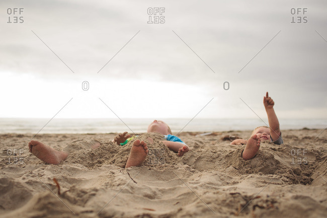 Boys covered themselves with sand on beach