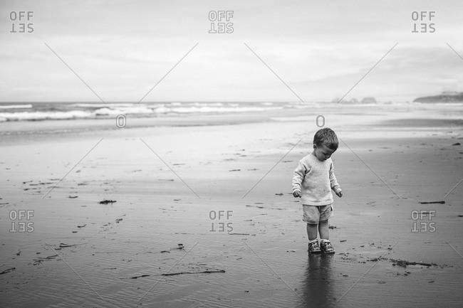 Boy standing on sandy beach