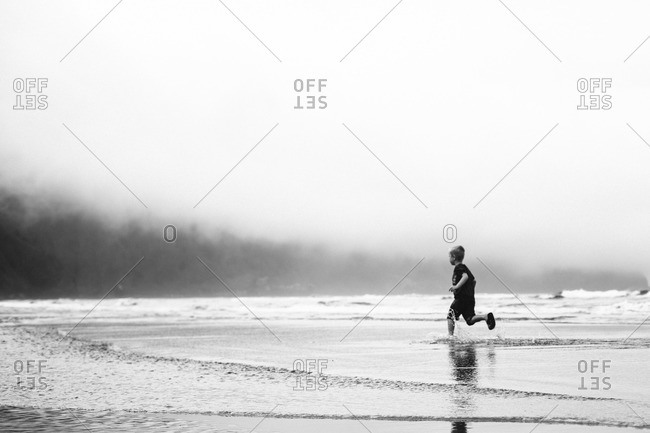 Young boy wading on beach