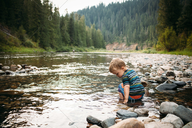 Boy squatting in shallow river